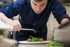 Closeup man garnishing food - stock photo