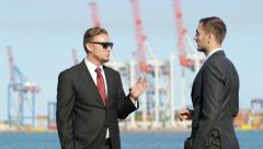 Two adult businessman talking about business standing in a sea port - stock footage