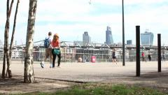 Tourists walk past Millennium Bridge with silver birch trees in foreground Stock Footage