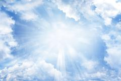 Bright sun shining in clouds Stock Photos