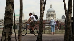Cyclists pass St Pauls Cathedral on Southbank of Thames Stock Footage