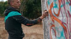 Graffiti artist drawing on the wall - stock footage