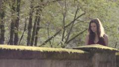 Beautiful Woman Crosses Moss Covered Stone Bridge In Sunlit Forest (Slow Motion) Stock Footage