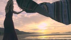 Young Woman Lays Out Picnic Blanket On Beach At Sunset (Slow Motion) Stock Footage