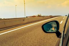 Young man driving a car reflected in the wing mirror Kuvituskuvat