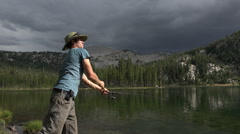 Young Man Casting Trout Fishing in Sierra Lake HD Stock Footage