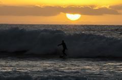 Orange Hard Sun with tidal wave Stock Photos