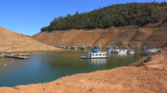 Houseboats sit in low water at Oroville Lake in California during extreme Stock Footage