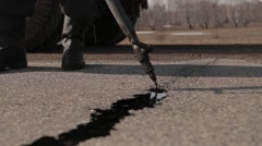 Sealing joint - crack in asphalt - stock footage