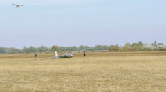 Plane  land on  soil field  with glider and people.  - stock footage