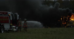 Firefighters putting out blaze in burning bus Stock Footage