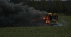 Stock Video Footage of Burnt out school bus in the middle of a field