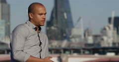 Portrait of a pensive businessman with London financial district in background. - stock footage