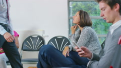 4K Friendly doctor talking to one of his patients in medical waiting area - stock footage