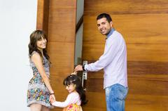 Adorable hispanic family of three posing for camera outside front entrance door - stock photo