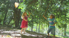 4K Happy little boy & girl playing in the woods with fishing nets - stock footage