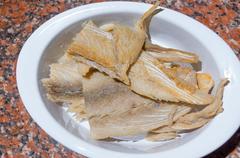 Pieces of dry fish lying on white plate drained in water, preparation fanesca - stock photo