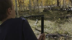 A boy shooting a bb gun while camping Stock Footage