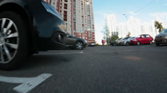 Parking lot with vehicles is in the inner yard of apartment building, low camera Stock Footage
