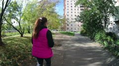 Young sportswoman in a bright pink jacket goes through the city park, rear view Stock Footage