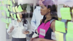 4K Mixed ethnicity business team brainstorming for ideas with sticky notes - stock footage