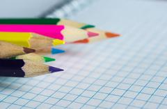 Stock Photo of Pencils of different colors on an open notebook