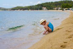 Little Girl Playing on the beach at the Aegean Sea. Stock Photos
