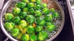 Blanching green brussels sprouts and carrots, at a restaurant kitchen - stock footage