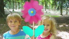 4K Happy little boy & girl playing in the woods with a pinwheel toy - stock footage