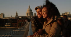 An attractive young couple on the Millenium Bridge enjoying a romantic moment. S Stock Footage