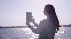 Happy woman reaches the coast, takes self portrait with tablet Stock Footage