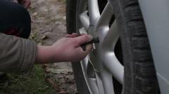 Man unscrews cap on wheel Stock Footage