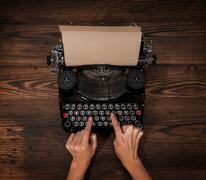 Stock Photo of Woman typing on an old typewriter
