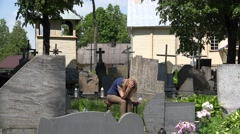 Painful widow woman shrink near father husband tomb in graveyard. 4K Stock Footage
