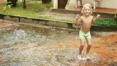 Happy smiling child having fun in the rain. Boy running through puddle. - stock footage