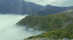 Fogs climb a steep hill in the mountains-timelapse Stock Footage
