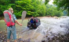 Tourist man with backpack and paddle watching the 4x4 vehicle crossing the river - stock photo