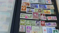 Watching an international stamp collection Stock Footage