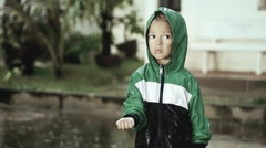 Poor lonely child staying alone in the rain. Cute sad boy is bored. Slow motion - stock footage