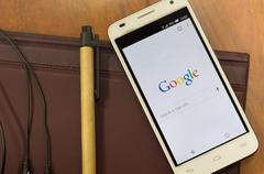 QUITO, ECUADOR - AUGUST 3, 2015: White smartphone lying on desk with Google - stock photo