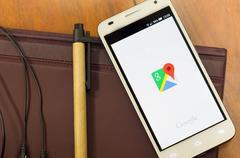 QUITO, ECUADOR - AUGUST 3, 2015: White smartphone lying on desk with Google maps Kuvituskuvat
