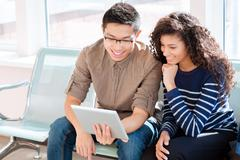 Asian boy and african american girl are using tablet computer Stock Photos
