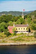 Buildings with flag in the Oslofjord - stock photo