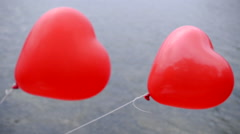 Heart-shaped balloons flying in the wind Stock Footage