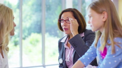 4K Friendly doctor talking to parent and child patient in office. - stock footage