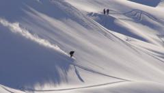 Skier riding down a snowy mountain jumping over some natural obstacles Stock Footage