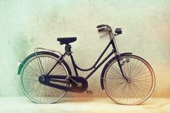 Beautiful Old rusty bicycle retro with awesome effect colors on grunge grey Stock Photos