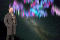 Stock Photo of Middle-aged man in a coat looking up on starry universe background with North
