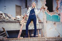 Blonde in the coat on the ruins of the house, beauty Stock Photos