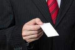 Unrecognizable businessman holding a card in hand Stock Photos